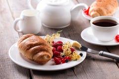 可口早餐用新鲜的新月形面包和成熟莓果 免版税库存图片