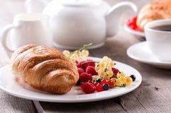 可口早餐用新鲜的新月形面包和成熟莓果 免版税库存照片