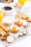 可口早餐用煮沸的鸡蛋和酥脆多士,顶视图 免版税库存图片