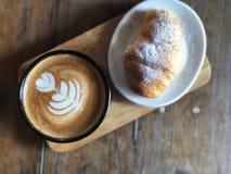 可口早餐;心脏爱拿铁在黑杯子和新月形面包的艺术咖啡冠上了用糖粉 免版税库存照片