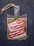 可口未加工的烟肉用在葡萄酒切板的迷迭香在木土气背景顶视图关闭 库存图片