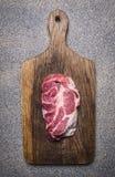 可口未加工的猪肉牛排葡萄酒切板木土气背景顶视图关闭 免版税库存图片