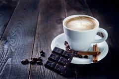可口杯子热奶咖啡用桂香和巧克力 免版税库存照片