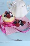 可口杯形蛋糕用莓果和葡萄酒糖罐在减速火箭的水色蓝色破旧的别致的桌上 免版税库存照片