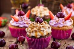 可口杯形蛋糕装饰用焦糖和新鲜的莓果 库存图片