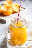 可口橙汁在玻璃瓶子的前景紧压了 免版税库存图片