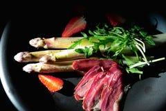 可口正餐 煮沸的芦笋、草莓、烟肉和hollands调味 库存照片