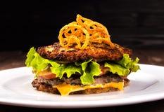 可口汉堡包土豆薄烤饼小圆面包 马铃薯饼汉堡用莴苣,乳酪,在木黑背景的蕃茄和 免版税库存图片