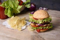 可口汉堡用牛肉、蕃茄、乳酪、莴苣和土豆片在木柜台 免版税图库摄影