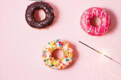 可口油炸圈饼为在粉红彩笔背景的生日 库存照片