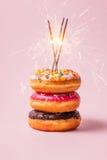 可口油炸圈饼为在粉红彩笔背景的生日 免版税图库摄影