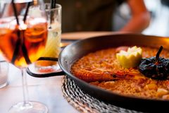 可口海鲜巴伦西亚肉菜饭特写镜头用国王大虾, aperol米用在平底锅的香料和玻璃喷鸡尾酒长的d 免版税库存图片