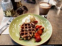 可口点心用奶蛋烘饼,草莓,奶油色和热巧克力与太阳镜夏天 免版税库存照片