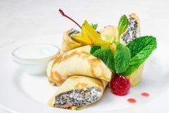 可口点心 薄煎饼用里面酸奶干酪和罂粟种子,长方形,装饰用莓果和薄菏 水平的框架 免版税库存图片
