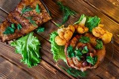 可口烤排骨和指关节,晒干用荷兰芹、莴苣、花椰菜和莳萝 被烘烤的肉在一木土气说谎 免版税库存照片
