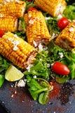 可口烤箱烹调了玉米用希腊白软干酪,辣椒粉,石灰,菜 免版税图库摄影