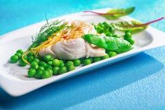 可口烤箱被烘烤的鱼片用豌豆 免版税库存图片