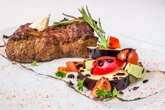 可口烤肉 烤肉、菜、调味汁和草本开胃大片断,在一块白色板材 水平的框架 免版税库存照片