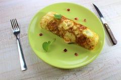 可口煎蛋滚动与刀子和叉子被隔绝的绿色板材和石榴 免版税图库摄影