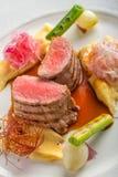 可口猪肉内圆角用土豆在白色板材和菜服务的饲料用调味汁,餐馆的产品摄影 库存照片