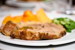 可口猪肉牛排用金黄被烘烤的土豆和沙拉在白色板材 免版税库存照片