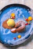 可口甜巧克力方旦糖用果子在蓝色板材、产品摄影餐馆的或法式蛋糕铺服务 免版税库存照片