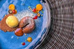 可口甜巧克力方旦糖用果子在蓝色板材、产品摄影餐馆的或法式蛋糕铺服务 免版税库存图片