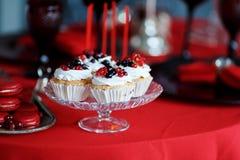 可口甜自助餐用在红色桌上的杯形蛋糕 免版税库存照片