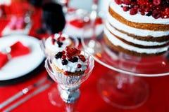 可口甜自助餐用在红色桌上的杯形蛋糕 免版税图库摄影