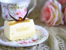 可口白色巧克力蛋糕和一杯美丽的茶为在软性的美妙的早晨弄脏了背景 库存图片