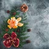 可口石榴石果子,普通话 桂香和茴香在黑暗的背景 概念新年度 平的位置 顶视图 库存图片