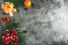 可口石榴石,普通话框架  桂香和茴香在黑暗的背景 新年概念圣诞节  平的位置 顶视图 库存图片