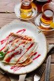 可口稀薄的薄煎饼服务用在一张木土气桌上的草莓调味汁 免版税库存图片