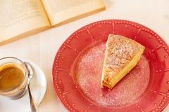 可口红萝卜饼片断在一本红色发光的板材和葡萄酒旧书的 一部分的在一块板材的一块自创杯形蛋糕用无奶咖啡 免版税图库摄影