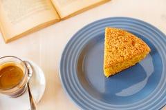 可口红萝卜饼片断在一本蓝色发光的板材和葡萄酒旧书的 一部分的在一块板材的一块自创杯形蛋糕有黑coffe的 库存照片