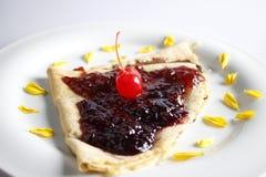 可口绉纱用果酱和樱桃 库存照片