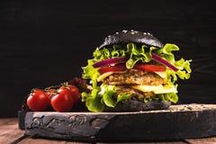 可口自创素食主义者黑色汉堡用两鸡豆炸肉排、蕃茄、乳酪、葱和沙拉在木桌上,黑暗 图库摄影