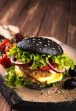 可口自创素食主义者黑色汉堡用两鸡豆炸肉排、蕃茄、乳酪、葱和沙拉在木桌上,黑暗 免版税库存图片