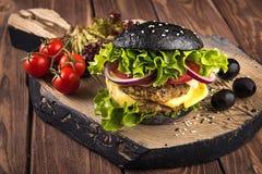 可口自创素食主义者黑色汉堡用两鸡豆炸肉排、蕃茄、乳酪、葱和沙拉在木桌上,黑暗 库存图片