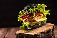 可口自创素食主义者黑色汉堡用两鸡豆炸肉排、蕃茄、乳酪、葱和沙拉在木桌上,黑暗 免版税图库摄影