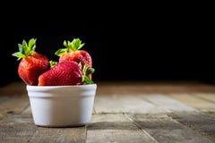 可口草莓在一张木桌上的一个自创厨房里 免版税图库摄影