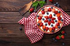 可口草莓饼用新鲜的蓝莓和打好的奶油在木土气桌,乳酪蛋糕上 免版税库存照片