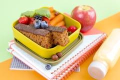 可口荷兰早餐用甜面包和莓果 孩子的食物在学校 学校辅助部件和练习簿 顶层 免版税库存照片