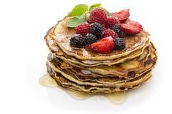 可口薄煎饼有莓果和枫蜜顶视图,白色背景 免版税库存图片