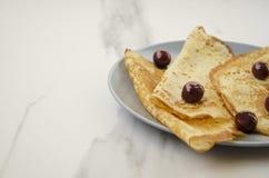 可口薄煎饼用在灰色桌上的樱桃 库存照片