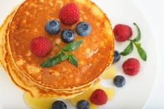可口薄煎饼用新鲜的蓝莓、莓和枫蜜 图库摄影
