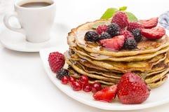 可口薄煎饼用莓果和枫蜜在白色背景 免版税库存图片