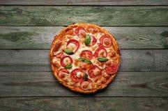 可口薄饼用乳酪和蕃茄在土气木桌上 图库摄影