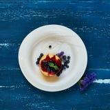 可口蛋糕服务用蓝莓、果酱和薄荷叶 免版税图库摄影