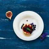 可口蛋糕服务用蓝莓、果酱和薄荷叶 免版税库存图片